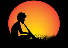 Man grass moon. Aboriginal man  sitting in the grass playing a didgeridoo Stock Image