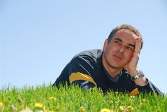 Man grass sky. Man lying on a grass on a background of blue sky with concerned expression Royalty Free Stock Photos