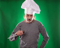The man with gray beard in a sailor suit and hat chef holding knife and vegetable Royalty Free Stock Images