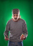 The man with gray beard in a sailor suit and hat chef holding knife and vegetable Royalty Free Stock Photos