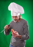 The man with gray beard in a sailor suit and hat chef holding knife and vegetable Royalty Free Stock Image
