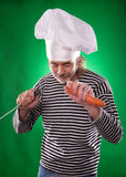 The man with gray beard in a sailor suit and hat chef holding knife and vegetable Stock Images