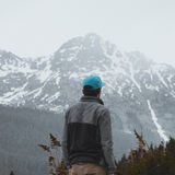 Man in Gray and Black Jacket Wearing Blue Baseball Cap Standing in Front of White and Gray Mountain during Daytime Royalty Free Stock Photos