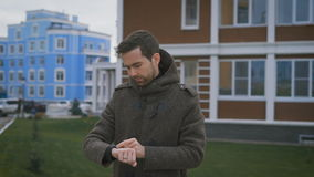 A man in a gray coat with a clock on hand and a ring on his finger is in the courtyard of his house. He changes the. A man in a gray coat with a clock on hand stock video footage