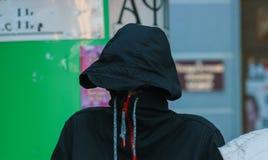 Man in gray cowl hiding his face stock photo