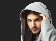 Man in gray cowl neck hoodie. Man posing in gray cowl neck hoodie, studio portrait, dark background Royalty Free Stock Image