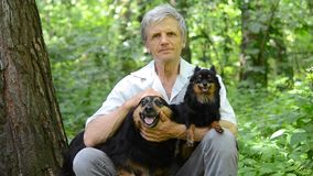 Man with gray hair and dog sitting in the forest