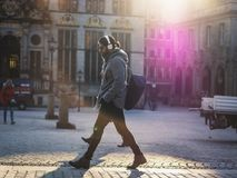 Man in Gray Hooded Jacket Walking on Gray Bricks Pavement Stock Photography