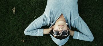 Man in Gray Hoodie Lying on Green Grass Royalty Free Stock Photo