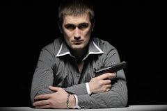 Man in gray shirt with gun Stock Photo