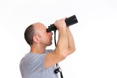 Man in gray shirt looking  through a binoculars Royalty Free Stock Photo
