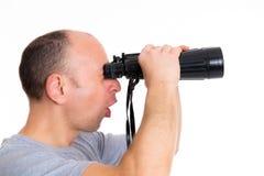 Man in gray shirt looking  through a binoculars Royalty Free Stock Photos