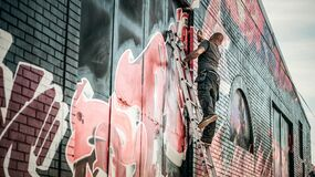 Man in Gray Shirt Standing on Gray Steel Ladder Painting Black White and Red Graffiti on Concrete Wall Outdoors Stock Photography