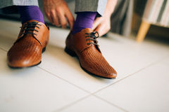 The man in gray slacks and a purple dress socks brown shoes with. Laces sitting on the couch Stock Photography