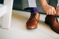 The man in gray slacks and a purple dress socks brown shoes with. Laces sitting on the couch Stock Images
