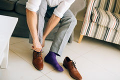 The man in gray slacks and a purple dress socks brown shoes with. Laces sitting on the couch Stock Image