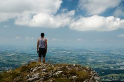 Man on Gray Sleeveless Shirt Standing on the Edge of Mountain Stock Photo