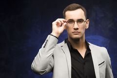 Man in a gray suit and glasses on a blue background. The young man in a gray suit and glasses on a blue background. Business portrait. Copy space Royalty Free Stock Photo