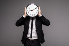 Man in gray suit holding big clock covering his face Royalty Free Stock Images