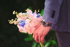 Man in Gray Suit Holding Bouquet of Pink and Blue Petaled Flowers Stock Image