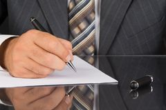 Man in gray suit holds a metal pen stock image
