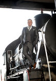 Man in gray suit posing on retro train Royalty Free Stock Image
