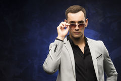 Man in a gray suit and sunglasses on a blue background. The young man in a gray suit and sunglasses on a blue background. Business portrait. Copy space Royalty Free Stock Photos