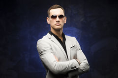 Man in a gray suit and sunglasses on a blue background. The young man in a gray suit and sunglasses on a blue background. Business portrait. Copy space Stock Images