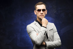 Man in a gray suit and sunglasses on a blue background. The young man in a gray suit and sunglasses on a blue background. Business portrait. Copy space Stock Photo