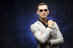 Man in a gray suit and sunglasses on a blue background. Stock Image