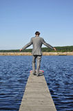 Man in a gray suit walking on the pier Stock Photo