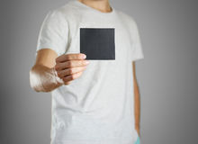 A man in a gray t-shirt holding blank clear black of the sheet. Royalty Free Stock Images