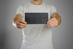 A man in a gray t-shirt holding blank clear black of the sheet. Royalty Free Stock Photography