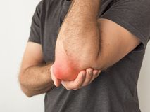 Man holds a painful elbow royalty free stock images