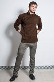 The man in gray trousers and fashionable brown sweater Stock Image