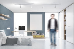 Man in a gray walled bedroom with study corner Royalty Free Stock Photo