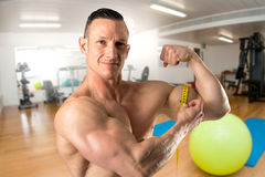 Man with great biceps. Man with powerful biceps using a measuring tape in the gym stock photos
