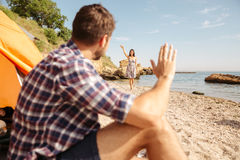 Man greating his girlfriend while sitting at the tent outdoors Royalty Free Stock Photos