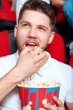 Man greedy eating popcorn in cinema Stock Photography