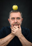 Man with a green apple on his head Stock Image