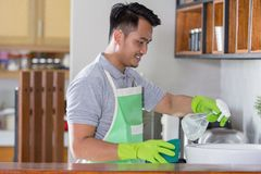 Man cleaning sink. Man with green apron and rubber gloves clean the sink Stock Photography