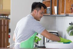 Man cleaning sink. Man with green apron and rubber gloves clean the sink Royalty Free Stock Image