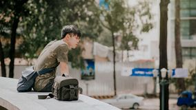 Man in Green and Beige Camouflage T-shirt Siting Beside Bag at Daytime Stock Photography