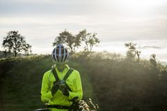 Man in Green Bicycle Suit Standing While Using His Smartphone Royalty Free Stock Photos