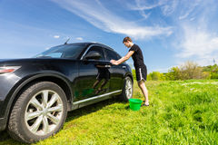 Man with Green Bucket Washing Car in Green Field Stock Photos