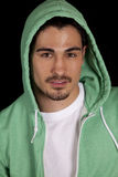 Man in green hoodie on black. A close up of a man in a green hoodie with a small smile on his lips Stock Images