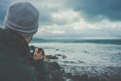 Man in Green Hoodie Holding Dslr Camera Near Seashore Under Gray Clouds Stock Photos