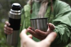 Man in green jacket offers a hot drink - tea or coffee from thermos to someone who pulls a hand, first person view royalty free stock photography