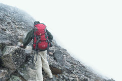Man in Green Jacket With Red and Black Backpack Climbing Mountain Stock Photo