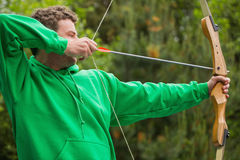 Man in green jumper about to shoot arrow Stock Photos